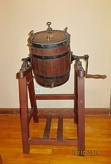 Barrel shaped oak container, rotating on pine framework or stand. Used in a farm environment to manually agitate cream to produce butter and buttermilk, the byproduct of butter production.