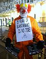 Clown with a reminder about Guantanomo and the dark side of American imperialism during a protest against Trump's inauguration outside the US Embassy in London.. (31627003633).jpg