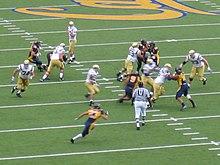 Un umpire osserva un'azione da dietro la linea della difesa durante una partite della NCAA.