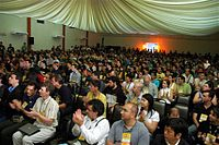An unrelated conference hall filled with clapping people. Large Group Awareness Training often takes place in conference-halls or hotels.