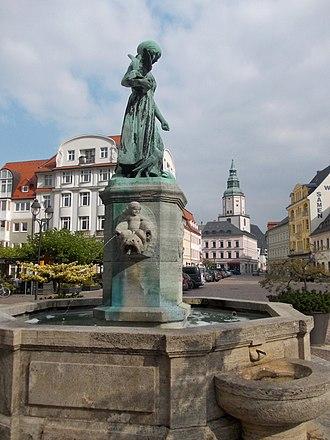 Döbeln - Schlegelbrunnen (fountain) with St Nicholas's Church in background