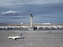 The Air Traffic Control Tower at Denver International Airport with a United Airlines Boeing 737-800 below.