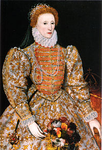 Woman, facing left, with a tiara on red-coloured hair, wearing voluminous and heavily decorated clothing with large sleeves, tight waist and a ruff round the neck. A crown on a table is visible in the background