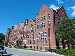 An elongated five-story reddish brown brick dormitory on a clear day