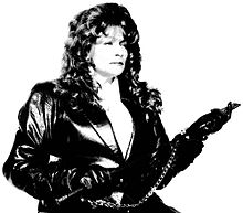 A black-and-white photograph of a woman with long, wavy hair wearing a black leather jacket, black leather gloves, and handcuffs