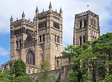 The two square front towers of a cathedral rising above some trees. Behind the paired towers is another taller square tower.