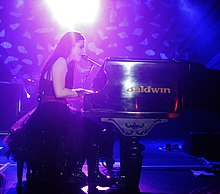 Young woman with long, dark hair singing and playing piano onstage