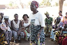 Traditional midwife in Africa at a community meeting, explaining the dangers of cutting for childbirth