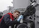 Fire Control Technician 2nd Class John Clausen conducts post-fire maintenance on a Phalanx CIWS aboard USS Nimitz (CVN-68).jpg