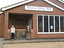 Frontage of a brick-built hall with two young children standing by the entrance.