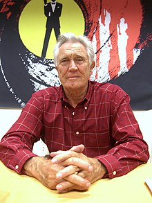 Grey haired man in red check shirt, sitting at a table on which his hands are resting.