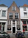 foto van Huis met in- en uitgezwenkte topgevel, winkelpui met middendeur en vensters tezamen een kozijn vormende