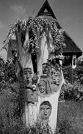 Ein Baumstumpf mit hinein geschnitzten Gesichtern von Hanns Mehner gestaltet