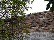 The bridge from the road, looking up through foliage at the east parapet wall with its unornamented date stone.