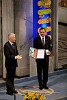 Deux hommes debout sur une scène.  L'homme à gauche tape dans ses mains et regarde vers l'autre homme.  Le deuxième homme sourit et montre deux objets à un public que l'on ne voit pas sur l'image.  Les articles sont un diplôme qui comprend une peinture et une boîte contenant une médaille d'or.  Derrière eux se trouve un pilier bleu vêtu de fleurs.