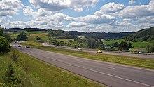Una autopista dividida que se curva a través de un paisaje rural a lo largo de un valle, subiendo ligeramente en el fondo.