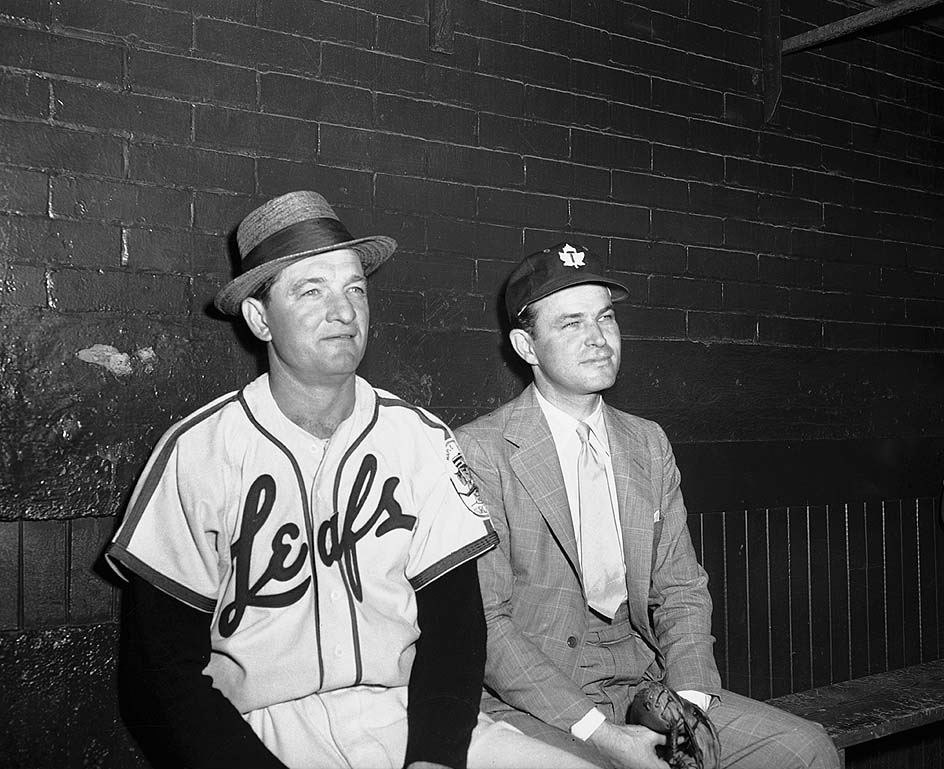 Jack Kent Cooke with baseball player in Toronto Maple Leafs Baseball Club dugout, Maple Leaf Stadium