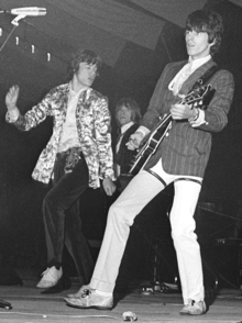 Black and white photo of three men performing on a stage, two of them in the foreground and one behind them