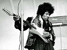 Una fotografía en blanco y negro de un hombre tocando una guitarra eléctrica.