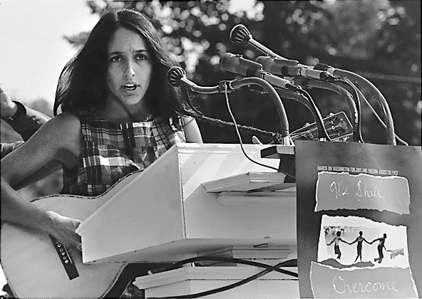 Baez stands behind a too-tall podium bristling with microphones, wearing a plaid sleeveless top, longish hair in a feather cut