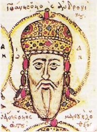 Head of an elderly white-bearded man, wearing a golden jewel-encrusted domed crown and surrounded by a halo.