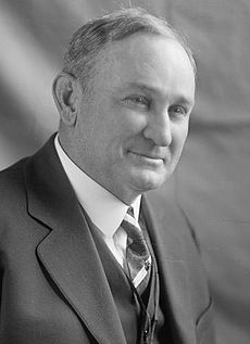 A man with thinning, salt-and-pepper hair wearing a black jacket and vest, white shirt, and patterned tie