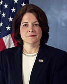 A female Caucasian wearing a blue suit with a white blouse and an American flag lapel pin. In the background is an American flag.