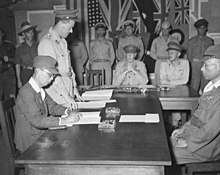 Men in uniform sit at a large wooden table. One is signing a document.