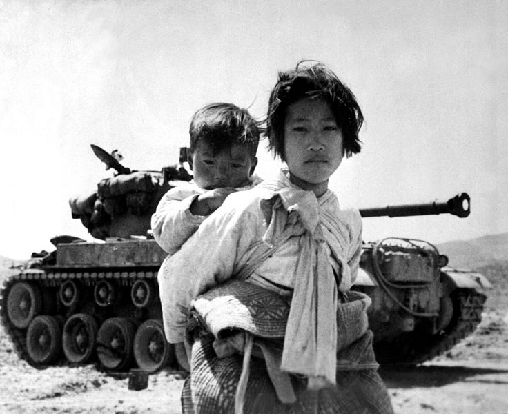 Korean civilians walk past a tank