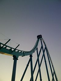 A photograph of a roller coaster train approaching a drop. The track is illuminated in green and blue under a dusk sky.