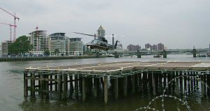 London Heliport - A Sikorsky S-76 landing at London Heliport. Battersea Railway Bridge is seen in the background.