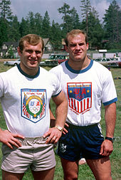 A pair of blonde haired male twins, wearing t-shirts and shorts emblazoned with the USA Olympic team logos.
