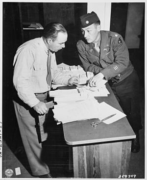 Provost marshal - Lieutenant Colonel James P. Smith, Jr., provost marshal of the Berlin District, left, and Major William J. E. Keish, commanding officer, 713th Military Police Battalion, check pass lists for the Potsdam Conference area in Potsdam, Germany on July 14, 1945