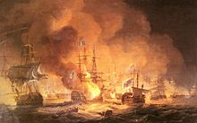 A confused naval battle. Two battered ships drift in the foreground while smoke and flames boil from a third. In the background smoke rises from a confused melee of battling ships.