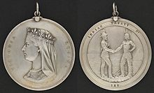 "Two sides of a silver medal: the profile of Queen Victoria and the inscription ""Victoria Regina"" on one side, a man in European garb shaking hands with an Aboriginal with the inscription Indian Treaty 187 on the other"