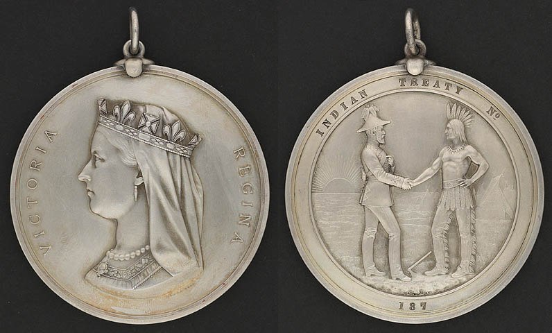 """Two sides of a silver medal: the profile of Queen Victoria and the inscription """"Victoria Regina"""" on one side, a man in European garb shaking hands with an Aboriginal with the inscription Indian Treaty No. 187 on the other"""