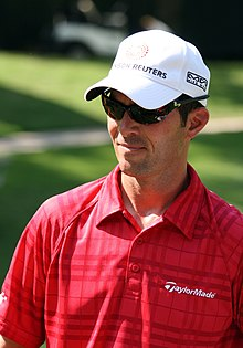 Upper body of a man in his thirties. He is wearing a red golf shirt, white baseball cap and dark sunglasses.