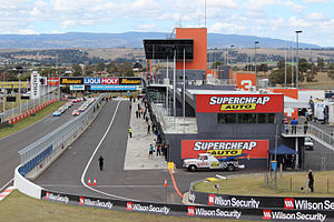 Mount Panorama Circuit - Pit Straight and the pit lane as viewed from Hell Corner, with cars lined up on the starting grid in preparation for a race.