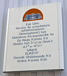 "A metallic white sign on a gray background with a red and blue depiction of a building at the top. Below it is text in blue saying ""Eye Clinic"" in English, French and the other nine official territorial languages"