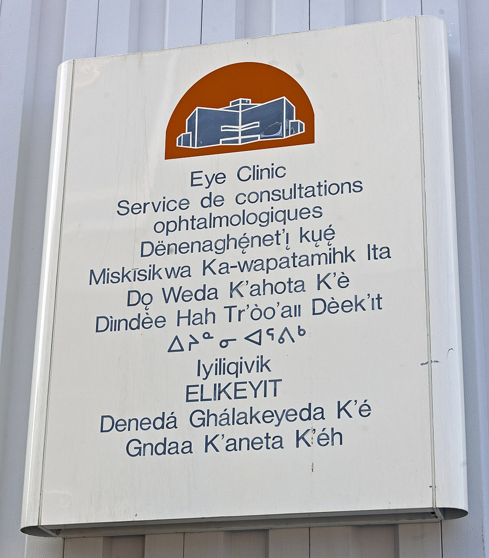 """A metallic white sign on a gray background with a red and blue depiction of a building at the top. Below it is text in blue saying """"Eye Clinic"""" in English, French and the other nine official territorial languages"""