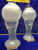 Two identical trophies, glass columns with globes on top, the left one closer to the camera, are pictured in front of a blue background.