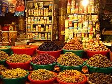 photo en couleurs, au premier plan des bassines en plastique remplies d'olives et de piments, au fond des étagères portent des boites de conserve et des bouteilles d'huile