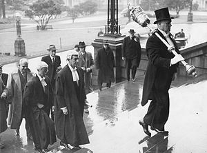 Monarchy of New Zealand - Serjeant-at-Arms carries the ceremonial mace at the Opening of the New Zealand Parliament in 1950. The mace represents the monarch's authority in parliament.