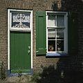 Overzicht van de deur met bovenlicht en van het venster met luiken rechts ernaast, in de voorgevel van de boerderij - Rouveen - 20387860 - RCE.jpg