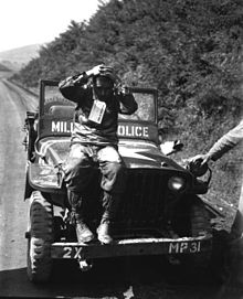 A man sits on a jeep with his hands on his head