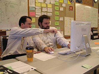 Agile software development - Pair programming, an agile development technique used by XP. Note information radiators in the background.