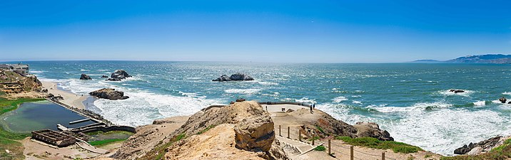 Panorama shows a wide, sweeping view of the view from an outcropping at Land's End. The Pacific Ocean shines a brilliant aquamarine and spectators can be see enjoying the ocean breeze on the clear summer day.