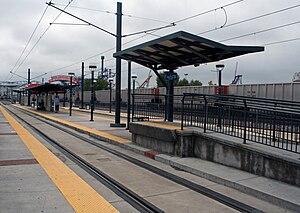 Pepsi Center–Elitch Gardens station - An empty coal train is passing by Pepsi Center - Elitch Gardens station on adjacent railroad tracks.