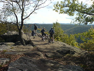Trail - Hikers and Mountainbikers on top of the Drachenfels (Dragons Rock) in the Palatinate Forest, Germany