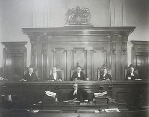 Supreme Court of Ontario - Group photograph of the justices of the Supreme Court of Ontario, Second Divisional Court. Depicted from left to right are: Justice Masten, Justice Riddell, Justice Latchford, Justice Middleton, and Justice Orde. A court clerk is seated below the bench. The photograph was taken in a courtroom at Osgoode Hall, ca. 1925